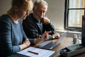 Couple âgé en reflexion devant un contrat