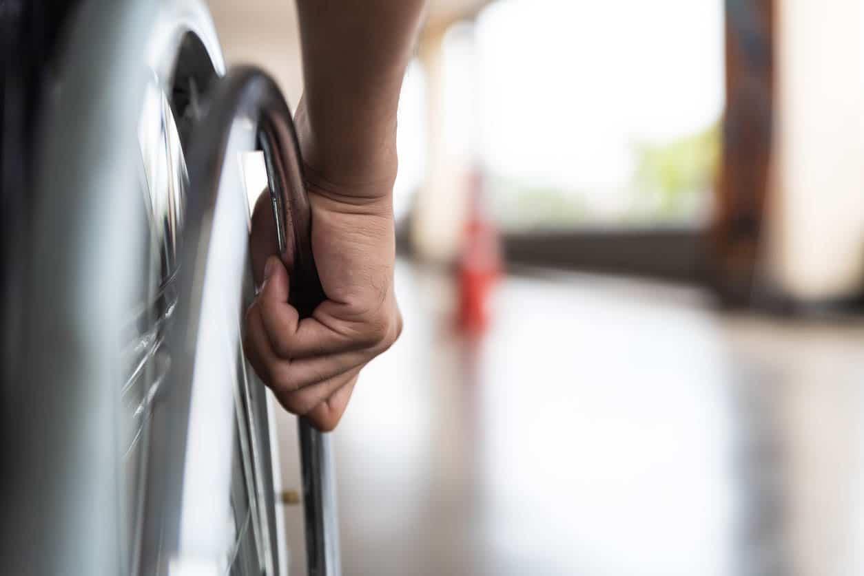 main de l'homme sur la roue de fauteuil roulant