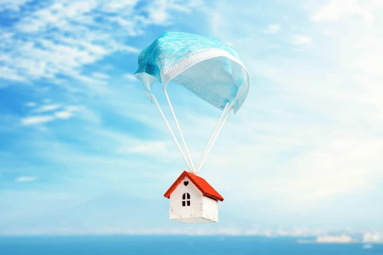 Une maison de jouet vole sur un parachute d'un masque médical