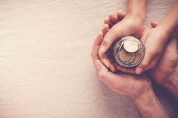 main enfant et adulte qui tienne une tirelire - concept de don