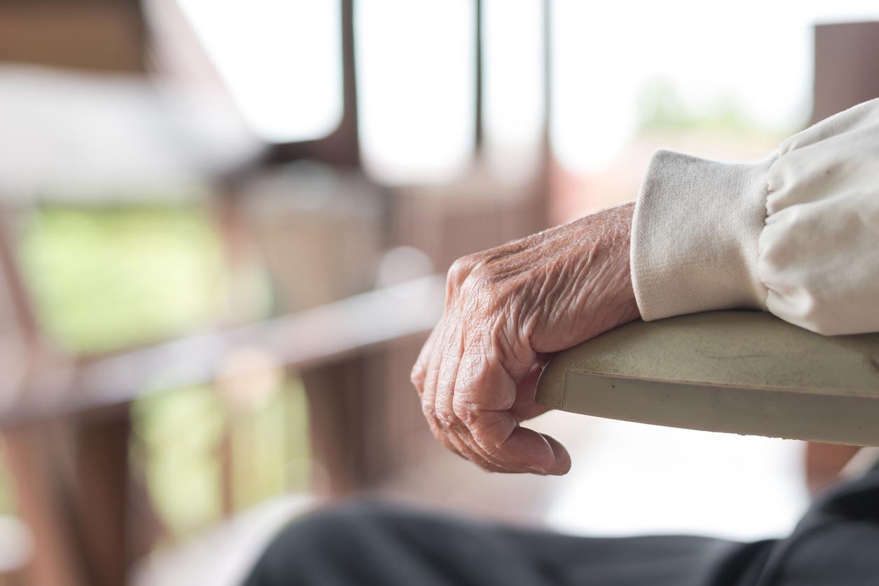 main d'une vieille femme sur un fauteuil roulant