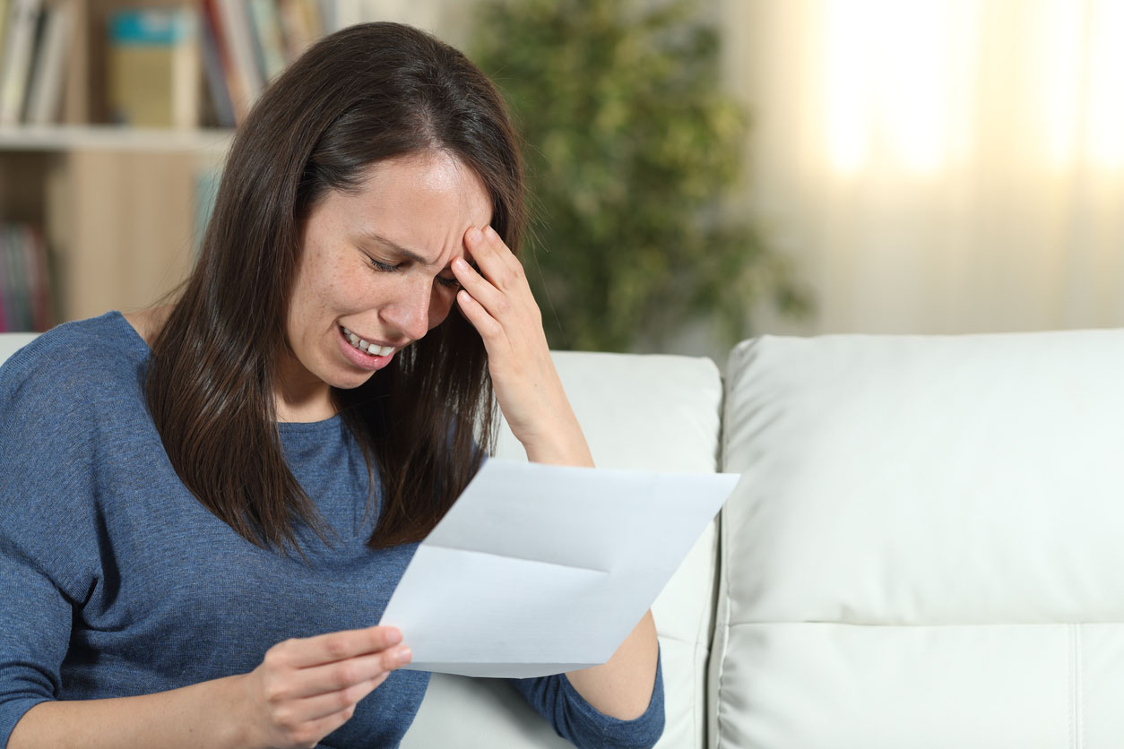 Sad Woman Reading A Letter On A Couch At Home
